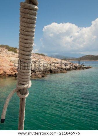 detail of ships stay with green sea rocky coast and blue summer sky behind - stock photo