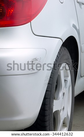Detail of silver car with scratch on the rear bumper - stock photo