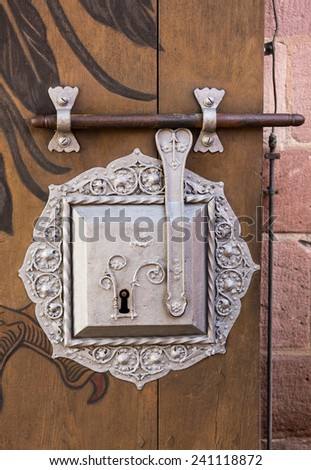 Detail of silver painted metal door lock and bar on grained solid wood door in Nuremberg Castle, Germany