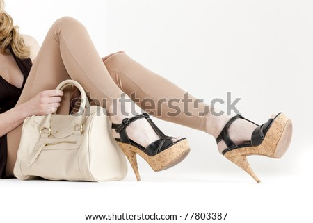 detail of sitting woman wearing summer shoes with a handbag - stock photo