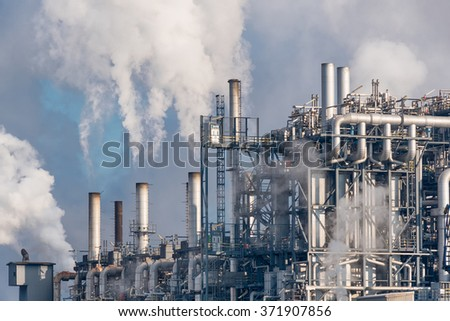 detail of smoking chimneys of a petrochemical factory in an oil refinery - stock photo