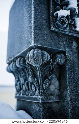 Detail of snow covered sculpture or pedestal of the grave in the cemetery of small town church.  - stock photo