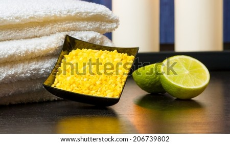 detail of spa massage border background with towel stacked candles sea salt and lime on wood table - stock photo