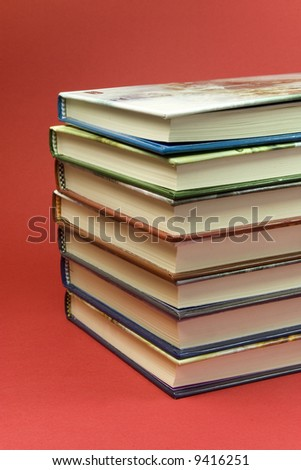 detail of 7 stack books on red background - stock photo