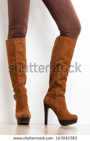 detail of standing woman wearing brown boots - stock photo