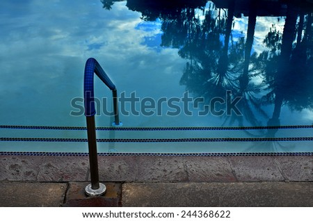Detail of swimming pool reflecting palm trees - stock photo