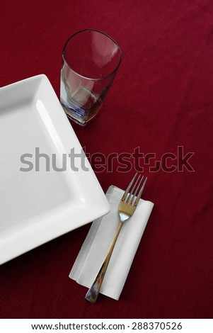 Detail of table place setting with plate cup fork and red table cloth - stock photo