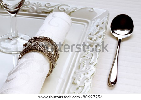 Detail of table setting in a chic restaurant with napkin ring and spoon - stock photo