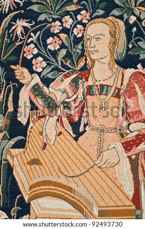 Detail of tapestry showing a Medieval woman playing a psaltery with a quill. - stock photo