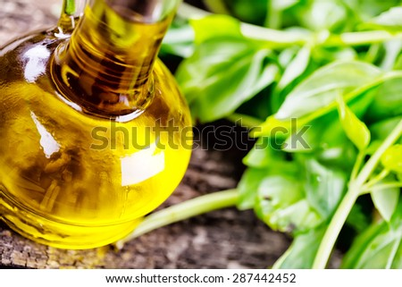 Detail of the bottle with sunflower oil on the background of greenery - stock photo