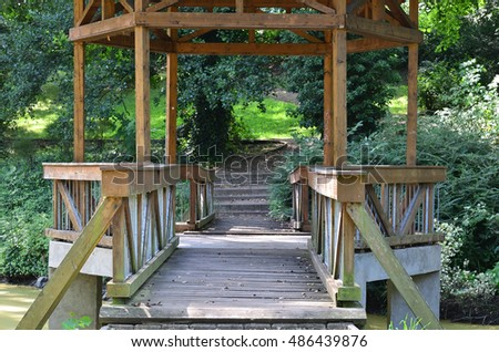 Detail of the bridge with the roof above the creek in the spa park in Klasterec nad Ohri in Czech republic.  /  Detail of the bridge