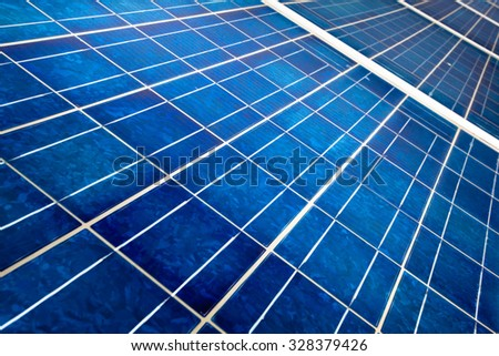 detail of the cells of a solar panel on a bright sunny day - stock photo