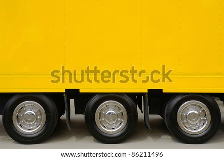 Detail of the empty yellow side of a large truck with three wheels - stock photo