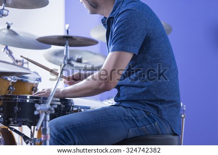 detail of the hands of a drummer is playing drums in a recording studio - focus on the left hand - stock photo