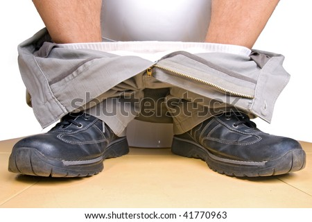 Detail of the legs of a man sitting on the toilet. A man sitting on a toilet bowl closeup. Pulled-down pants with boots on the toilet. Pants down with shoes man on the toilet. - stock photo