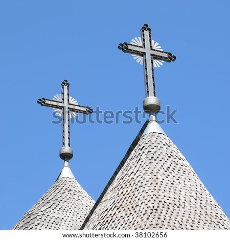 Detail of the roof of a shingle roof of a church with two crosses