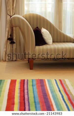 Detail of the sofa in the room with color-striped carpet - stock photo