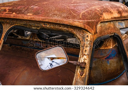 Detail of the wreckage side mirror of an rusty car in garage - stock photo