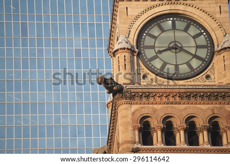 Detail of Toronto's city hall tower clock against modern building