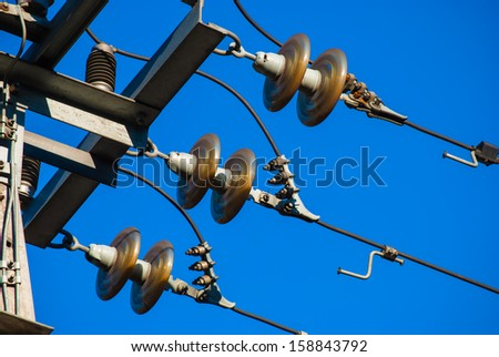 detail of transmission line tower against blue sky - stock photo
