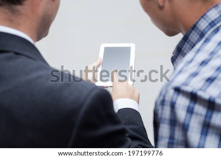 Detail of two businessmen using digital tablet. - stock photo
