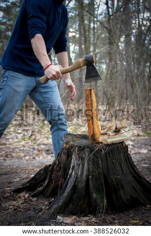 Detail of two flying pieces of wood on log with sawdust. Man is chopping wood with vintage axe. Frozen moment