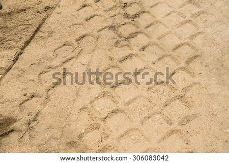 Detail of tyre tracks in sand on building bridge - stock photo