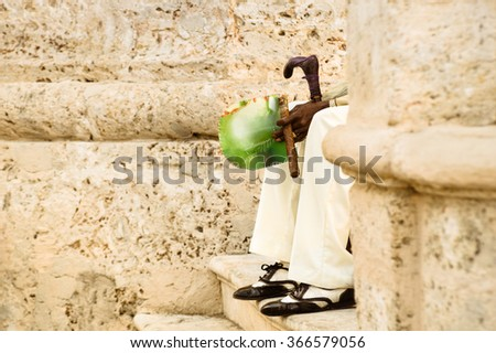 Detail of unrecognizable person with cuban cigar sitting on stairs at Havana old city in Cuba - Indigenous man wearing traditional clothing and accessories  - Warm color tones with focus on hands - stock photo