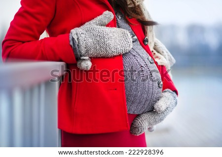 Detail of unrecognizable pregnant woman's belly in winter - stock photo