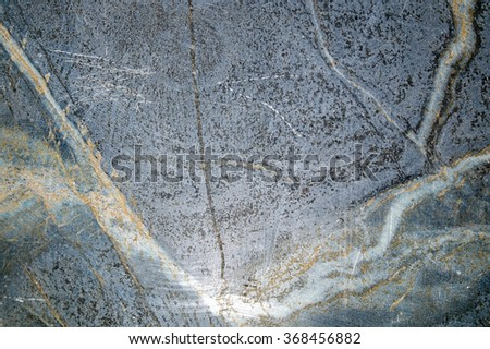 Detail of veins and scratches in large slab of black soapstone. - stock photo