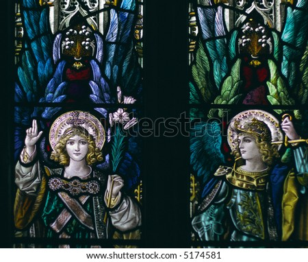 detail of victorian stained glass church window in Fringford depicting two typical victorian angels with a sword and a lily in their hands - stock photo