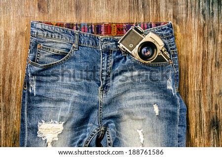 Detail of vintage jeans with classic camera in the pocket - stock photo
