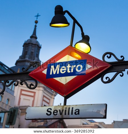 Detail of Vintage Sevilla Metro Station Sign in Madrid Spain, illuminated in dusk.
