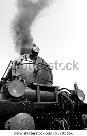 Detail of Vintage steam engine, working, with smoke, against blue sky - converted to Black and white