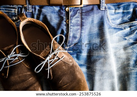 Detail of vintage style shoes on denim jeans - stock photo