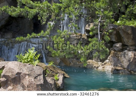 Detail of water feature with pine trees in a Japanese garden. - stock photo