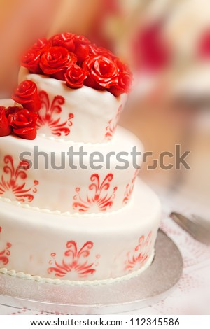 Detail of wedding cake with red roses - stock photo