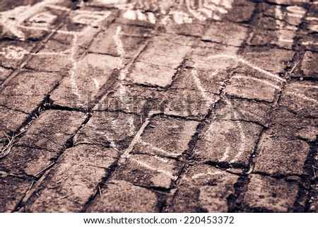Detail of white kid's chalk drawing on the bricks. Black and white photography. Retro filtered. Monochrome cream tone. - stock photo