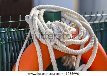 Detail of white rope and float in the lifeguard post of a swimming pool - stock photo