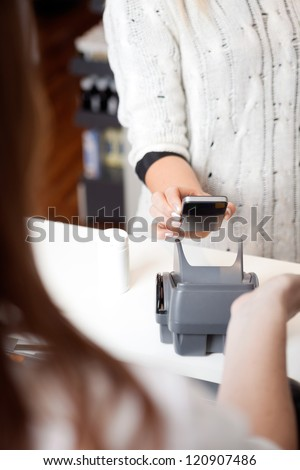Detail of woman paying for good with NFC technology on mobile phone - stock photo