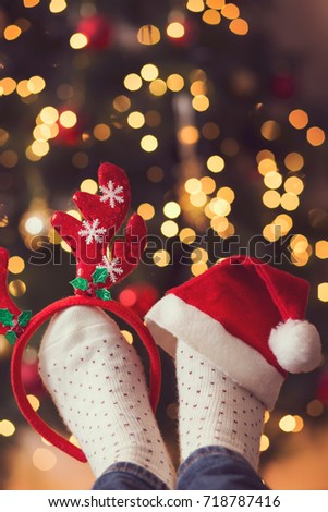 Detail of woman's feet wearing warm winter socks and small antlers and Santa's hat, placed on the table with nicely decorated Christmas tree and Christmas lights in the background. Selective focus
