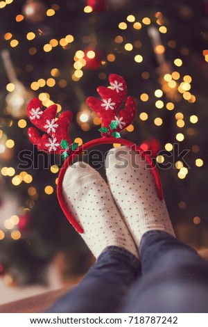 Detail of woman's feet wearing warm winter socks and small antlers, placed on the table with nicely decorated Christmas tree and Christmas lights in the background. Selective focus on the antlers