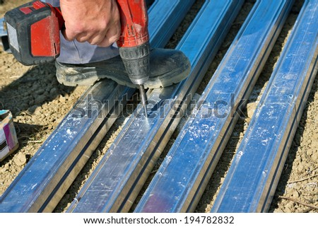 Detail of worker fixing nuts with electric screwdrivers on construction frames - stock photo