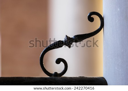 Detail of wrought iron work with an ornamental curlicue in the angle between a wall and rail or balustrade - stock photo