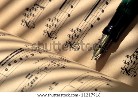 Detail of 100 year old grungy sheet music with vintage fountain pen. - stock photo