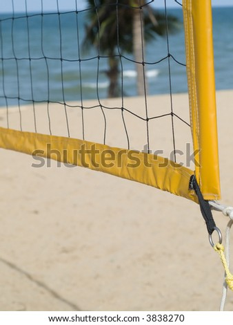 Detail of yellow and black volleyball net on the beach. Shallow depth of field, with the beach out of focus. - stock photo