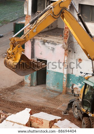 Detail of Yellow Digger Near Building Under Demolition - stock photo