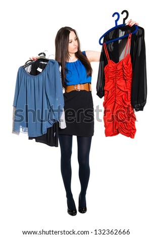 Detail of young woman choosing which dress to wear, isolated on white background - stock photo