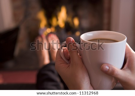Detail of young woman holding cup of coffee by fire - stock photo