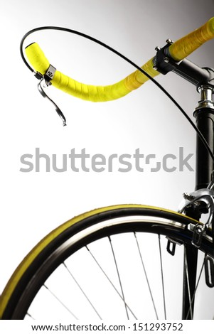 Detail on a handlebar and wheel of a bicycle - stock photo